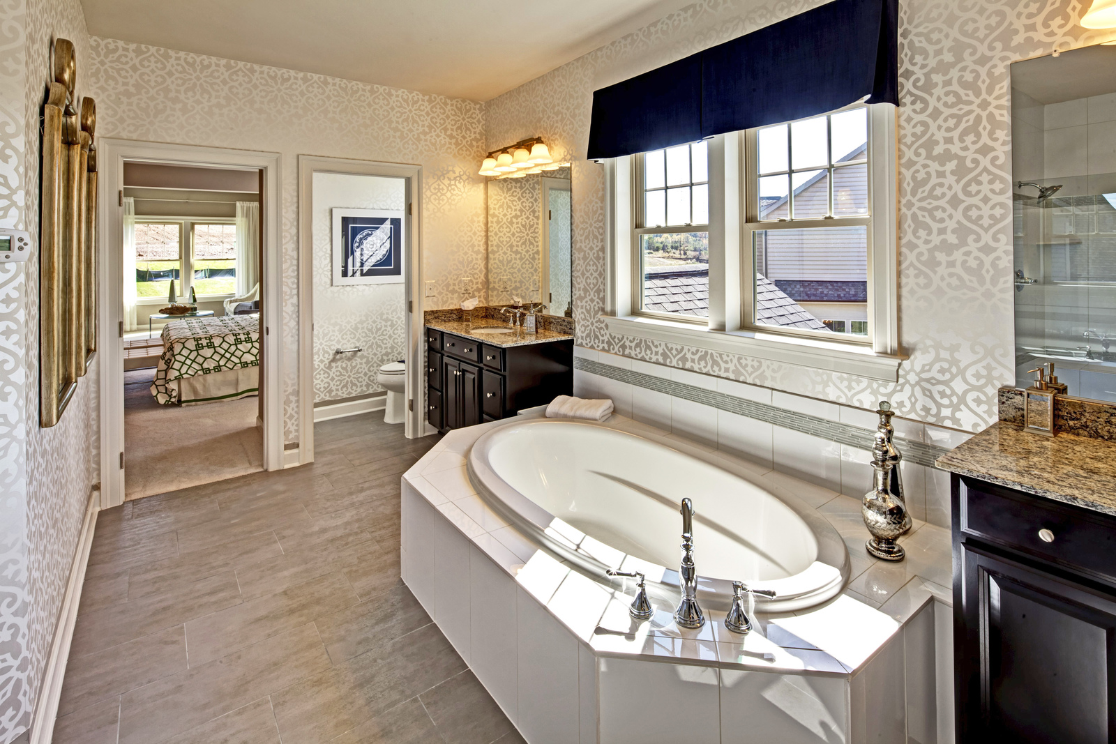 The owner's bath invites you to linger, featuring a generously deep soaking tub, comfort height double vanity with granite countertop, ceramic tile shower with rainmaker showerhead and premium, fixtures.