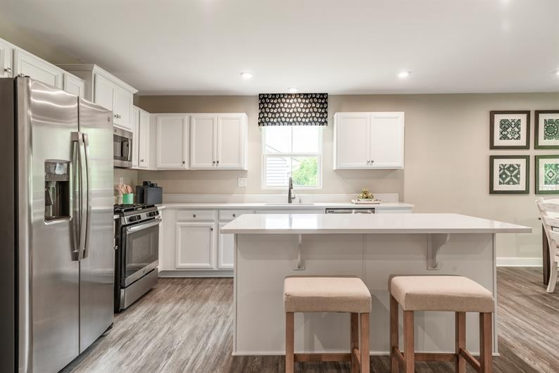 LUXURY FEATURES INCLUDE GRANITE, STAINLESS STEEL APPLIANCES, UPGRADED FLOORING AND EXTERIOR STONE