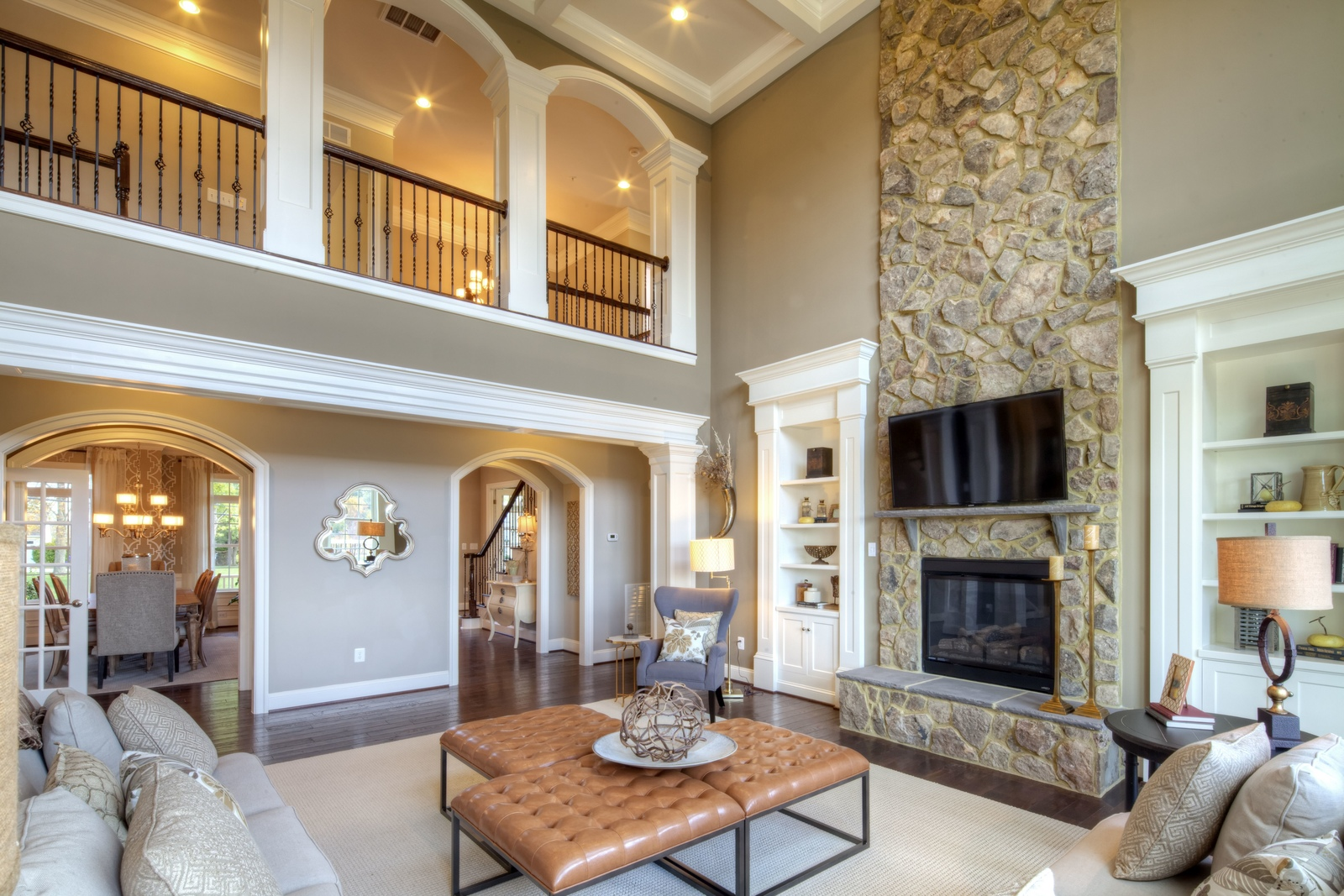 Two story great room offering a floor to ceiling stone fireplace, coffered ceiling, and built in bookcases