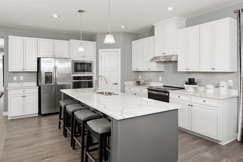 OPEN CONCEPT KITCHENS WITH BRAND NEW APPLIANCES AND OVERSIZED EATING ISLANDS