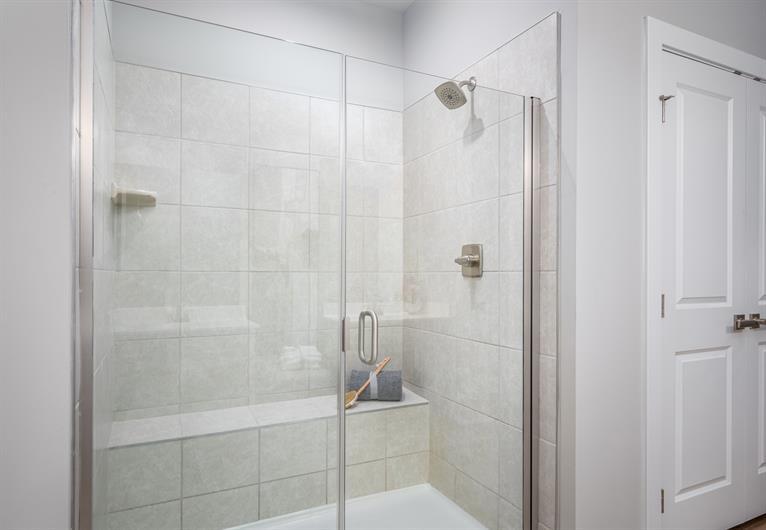 Owner's Shower Features a Framless Glass Door
